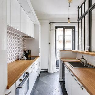 パリの中サイズのコンテンポラリースタイルのおしゃれなキッチン (白いキャビネット、木材カウンター、シルバーの調理設備、グレーの床、ドロップインシンク、フラットパネル扉のキャビネット、マルチカラーのキッチンパネル、セメントタイルのキッチンパネル、アイランドなし、セラミックタイルの床) の写真