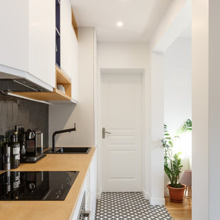 This is an example of a small modern single-wall open plan kitchen in Paris with a drop-in sink, flat-panel cabinets, white cabinets, wood benchtops, black splashback, terra-cotta splashback, stainless steel appliances, cement tiles, no island, multi-coloured floor and beige benchtop.