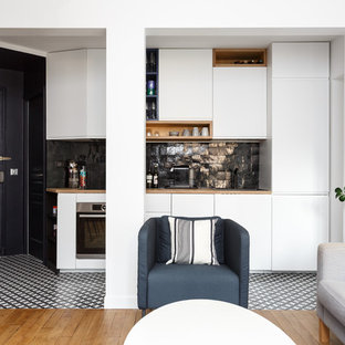 Photo of a small modern single-wall open plan kitchen in Paris with a drop-in sink, flat-panel cabinets, white cabinets, wood benchtops, black splashback, terra-cotta splashback, stainless steel appliances, cement tiles, no island, multi-coloured floor and beige benchtop.
