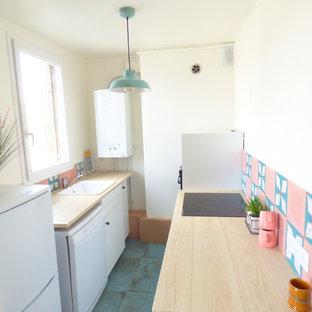 パリの中くらいのエクレクティックスタイルのおしゃれなキッチン (シングルシンク、フラットパネル扉のキャビネット、白いキャビネット、木材カウンター、ピンクのキッチンパネル、セメントタイルのキッチンパネル、黒い調理設備、セラミックタイルの床、緑の床、茶色いキッチンカウンター) の写真