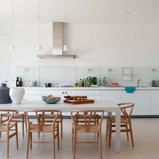 Idée de décoration pour une grande cuisine américaine linéaire design avec un placard à porte plane, des portes de placard blanches, une crédence en feuille de verre et un électroménager encastrable.