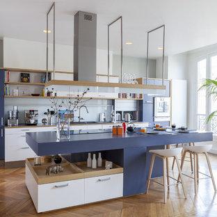 Cette image montre une cuisine design avec un placard à porte plane, des portes de placard blanches, une crédence blanche, une crédence en feuille de verre, un îlot central et un sol en bois brun.