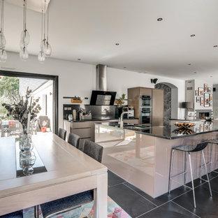 Ispirazione per una grande cucina contemporanea con lavello sottopiano, ante lisce, ante marroni, top in granito, paraspruzzi nero, pavimento con piastrelle in ceramica, isola, pavimento nero e top nero