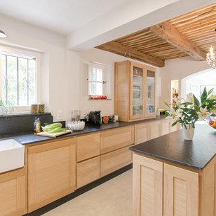 Cette image montre une grande cuisine américaine méditerranéenne avec un évier de ferme, des portes de placard en bois clair, une crédence noire, un sol en carrelage de céramique, un îlot central, un sol beige et un placard à porte shaker.