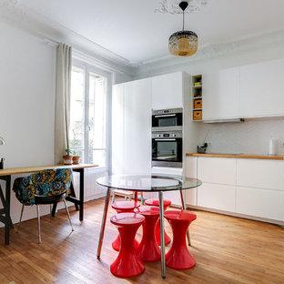 Exemple d'une cuisine ouverte linéaire éclectique avec un évier posé, un placard à porte plane, des portes de placard blanches, un plan de travail en bois, une crédence blanche, un électroménager en acier inoxydable, un sol en bois brun, aucun îlot et un sol marron.