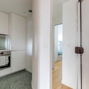Imagen de cocina en L, clásica, pequeña, cerrada, con fregadero integrado, armarios con rebordes decorativos, puertas de armario blancas, encimera de laminado, salpicadero gris, salpicadero de azulejos de terracota, electrodomésticos con paneles, suelo de terrazo, suelo verde y encimeras blancas