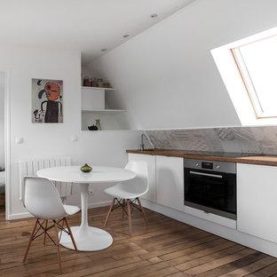 Cette photo montre une petit cuisine américaine linéaire tendance avec un évier encastré, des portes de placard blanches, un plan de travail en bois, une crédence grise, un électroménager en acier inoxydable et un sol en bois brun.