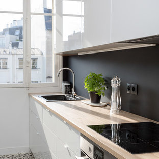 Inspiration for a mid-sized contemporary single-wall separate kitchen in Paris with wood benchtops, no island, a drop-in sink, flat-panel cabinets, white cabinets, black splashback, slate splashback, stainless steel appliances, slate floors, multi-coloured floor and beige benchtop.