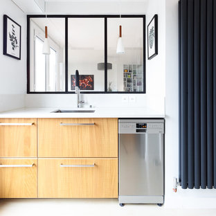 Réalisation d'une petit cuisine nordique fermée avec un évier encastré, un placard à porte plane, des portes de placard en bois clair, une crédence blanche, un électroménager en acier inoxydable, un sol blanc, un plan de travail blanc, un plan de travail en quartz et aucun îlot.