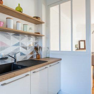 Aménagement d'une cuisine scandinave fermée avec un évier posé, un placard à porte plane, des portes de placard blanches, un plan de travail en bois et un plan de travail marron.