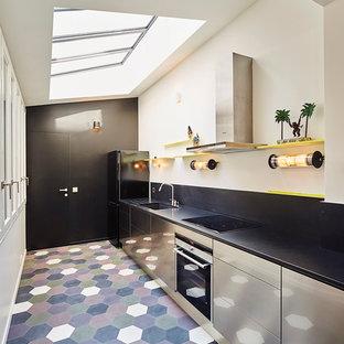 Idée de décoration pour une cuisine parallèle design avec un évier 1 bac, un placard à porte plane, une façade en inox, une crédence noire, aucun îlot, un sol multicolore et un électroménager noir.