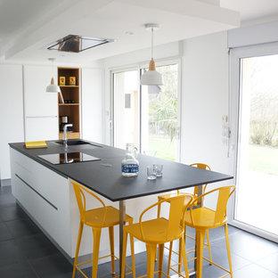 Aménagement d'une cuisine ouverte contemporaine de taille moyenne avec un évier intégré, un placard à porte plane, des portes de placard blanches, un îlot central et béton au sol.