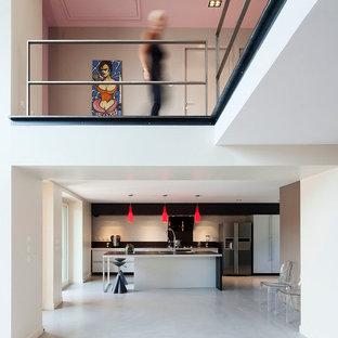 Inspiration pour une grande cuisine ouverte linéaire design avec un électroménager en acier inoxydable, un îlot central, des portes de placard blanches et une crédence blanche.