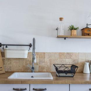 リヨンの大きいカントリー風おしゃれなキッチン (シングルシンク、フラットパネル扉のキャビネット、白いキャビネット、ラミネートカウンター、ベージュキッチンパネル、石タイルのキッチンパネル、パネルと同色の調理設備、セラミックタイルの床、茶色い床) の写真