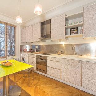 Idées déco pour une cuisine américaine linéaire contemporaine de taille moyenne avec un évier 1 bac, des portes de placard blanches, une crédence métallisée, un électroménager en acier inoxydable, un sol en bois brun et aucun îlot.