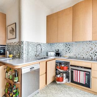 Exemple d'une grande cuisine chic fermée avec un évier encastré, des portes de placard en bois clair, un électroménager en acier inoxydable, aucun îlot, une crédence grise et une crédence en carreau de miroir.