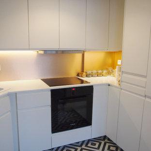 パリの小さいエクレクティックスタイルのおしゃれなキッチン (ダブルシンク、フラットパネル扉のキャビネット、白いキャビネット、ラミネートカウンター、オレンジのキッチンパネル、パネルと同色の調理設備、セメントタイルの床、アイランドなし、マルチカラーの床) の写真