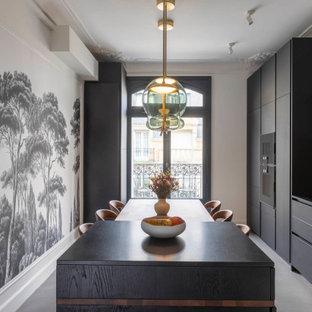 Aménagement d'une grand cuisine linéaire contemporaine fermée avec un évier encastré, des portes de placard noires, un plan de travail en granite, une crédence métallisée, un électroménager encastrable, béton au sol, un îlot central, un sol gris et un plan de travail noir.