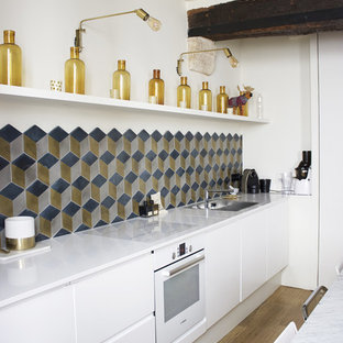 Mid-sized contemporary single-wall open plan kitchen in Paris with an undermount sink, quartzite benchtops, multi-coloured splashback, cement tile splashback, white appliances, light hardwood floors, flat-panel cabinets, white cabinets, no island and brown floor.