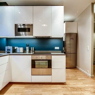 Aménagement d'une cuisine contemporaine en L fermée et de taille moyenne avec un évier encastré, un placard à porte plane, des portes de placard blanches, une crédence bleue, un électroménager en acier inoxydable, un sol en bois clair et aucun îlot.