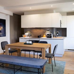 Idées déco pour une cuisine américaine contemporaine en L avec un évier encastré, un placard à porte plane, des portes de placard blanches, une crédence grise, un électroménager en acier inoxydable, un sol en bois brun, 2 îlots, un sol marron et un plan de travail blanc.