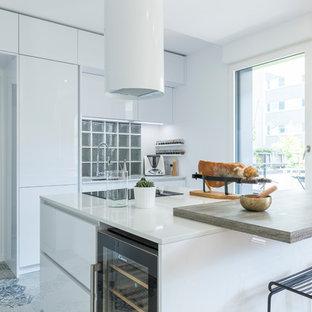 Cette image montre une cuisine américaine design avec un évier encastré, des portes de placard blanches, un plan de travail en quartz, un sol en carrelage de céramique, un îlot central et un sol beige.