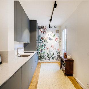 Foto på ett mycket stort funkis vit linjärt kök med öppen planlösning, med en undermonterad diskho, släta luckor, blå skåp, bänkskiva i kvartsit, vitt stänkskydd, svarta vitvaror och cementgolv