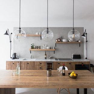 パリの広いインダストリアルスタイルのおしゃれなキッチン (アンダーカウンターシンク、フラットパネル扉のキャビネット、中間色木目調キャビネット、グレーのキッチンパネル、コンクリートの床、グレーの床、黒い調理設備、アイランドなし) の写真