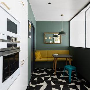 Foto di una cucina ad U design di medie dimensioni con lavello a vasca singola, ante bianche, paraspruzzi verde, elettrodomestici bianchi, pavimento in gres porcellanato, pavimento nero e top bianco