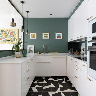 Bild på ett mellanstort funkis vit vitt u-kök, med vita skåp, grönt stänkskydd, vita vitvaror, klinkergolv i porslin, en undermonterad diskho, släta luckor och flerfärgat golv