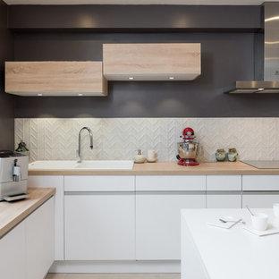 Aménagement d'une cuisine ouverte scandinave en L de taille moyenne avec un évier posé, des portes de placard blanches, un plan de travail en bois, un îlot central, un sol beige, un placard à porte affleurante, une crédence blanche, une crédence en feuille de verre, un électroménager en acier inoxydable et un sol en bois clair.