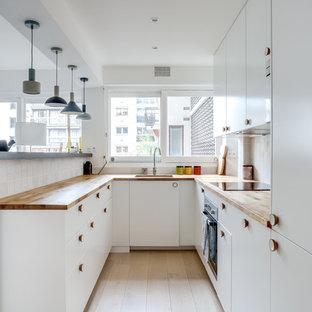 Inspiration pour une cuisine nordique en U avec un évier encastré, un placard à porte plane, des portes de placard blanches, un plan de travail en bois, une crédence blanche, une crédence en mosaïque, un électroménager noir, un sol en bois clair, une péninsule et un sol beige.