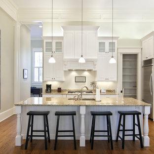 Cette photo montre une cuisine chic en L avec un placard avec porte à panneau surélevé, des portes de placard blanches, une crédence blanche, un électroménager en acier inoxydable, un sol en bois brun, un îlot central et un sol marron.