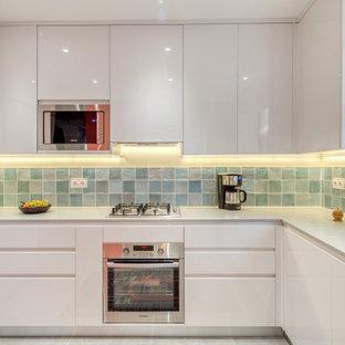 Réalisation d'une cuisine design en U de taille moyenne avec un évier encastré, un placard à porte plane, des portes de placard blanches, une crédence verte, un électroménager en acier inoxydable, un sol gris et un plan de travail blanc.