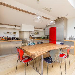 Idées déco pour une cuisine américaine industrielle en U avec un placard à porte plane, une façade en inox, un plan de travail en bois, une crédence métallisée, un électroménager de couleur, un sol en bois clair et un sol beige.