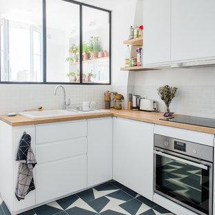 Inspiration pour une cuisine design avec un évier posé, un placard à porte plane, des portes de placard blanches, un plan de travail en bois, une crédence grise, aucun îlot et un plan de travail beige.