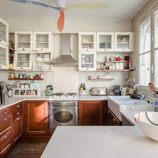 Exemple d'une cuisine éclectique en U avec une péninsule, un évier de ferme, un placard à porte vitrée, un électroménager en acier inoxydable, un sol en bois foncé, un sol marron, des portes de placard beiges, une crédence beige et un plan de travail beige.
