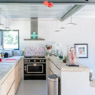 モンペリエのインダストリアルスタイルのおしゃれなペニンシュラキッチン (ドロップインシンク、フラットパネル扉のキャビネット、淡色木目調キャビネット、マルチカラーのキッチンパネル、黒い調理設備、白い床、ベージュのキッチンカウンター) の写真