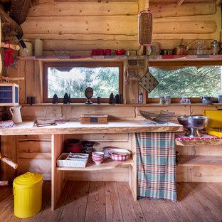 Cette photo montre une petit cuisine montagne fermée avec un placard sans porte, des portes de placard en bois brun, un plan de travail en bois, un sol en bois brun, aucun îlot, une crédence marron et une crédence en bois.