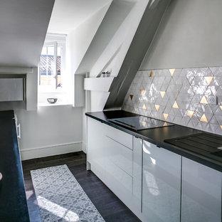 Idées déco pour une cuisine ouverte parallèle éclectique avec un évier encastré, des portes de placard blanches, un plan de travail en stratifié, une crédence blanche, une crédence en mosaïque, un électroménager noir, un sol en contreplaqué, un îlot central et un sol marron.