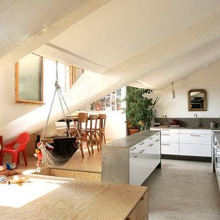 Cette photo montre une cuisine ouverte tendance en L de taille moyenne avec un placard à porte plane, des portes de placard blanches et un îlot central.