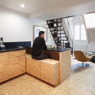 Inredning av ett industriellt mellanstort svart svart kök, med en undermonterad diskho, skåp i ljust trä, svart stänkskydd, svarta vitvaror, ljust trägolv, en köksö, gult golv och luckor med profilerade fronter