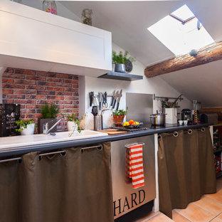 Cette photo montre une petite cuisine ouverte linéaire nature avec un évier posé, un électroménager en acier inoxydable, un sol en carreau de terre cuite et aucun îlot.