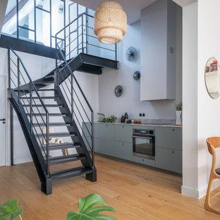 Cette image montre une cuisine ouverte linéaire urbaine de taille moyenne avec des portes de placard bleues, un plan de travail en granite, un électroménager en acier inoxydable, aucun îlot, un placard à porte plane, un sol en bois brun et un plan de travail gris.