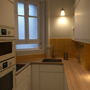 Photo of a small scandinavian u-shaped separate kitchen in Paris with a single-bowl sink, beaded inset cabinets, white cabinets, laminate benchtops, yellow splashback, ceramic splashback, panelled appliances, terrazzo floors and multi-coloured floor.