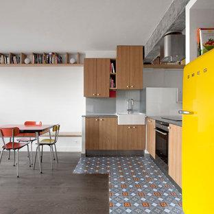 Idée de décoration pour une cuisine américaine design en L de taille moyenne avec un évier de ferme, des portes de placard en bois brun, une crédence grise, une crédence en feuille de verre, un électroménager encastrable et un sol en carrelage de céramique.