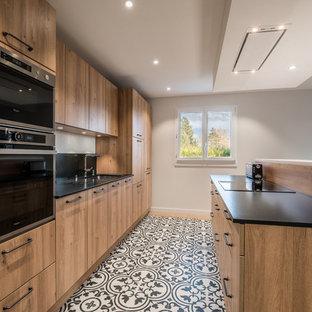 Cette photo montre une cuisine ouverte parallèle tendance de taille moyenne avec un évier encastré, un placard à porte plane, des portes de placard en bois brun, un électroménager noir, un sol en carreaux de ciment, un îlot central et une crédence noire.