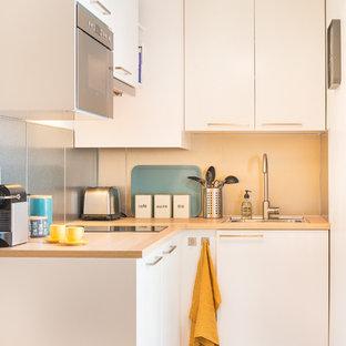Exemple d'une petite cuisine scandinave en L fermée avec un placard à porte plane, des portes de placard blanches et un plan de travail en bois.