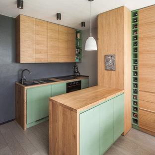 Cette photo montre une petit cuisine américaine parallèle scandinave avec un évier 1 bac, un placard à porte affleurante, des portes de placard en bois clair, un plan de travail en bois, une crédence noire, un électroménager encastrable, un sol en bois peint et un sol gris.