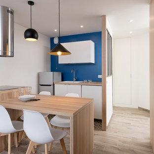 Exemple d'une cuisine américaine parallèle tendance avec un évier posé, un placard à porte plane, des portes de placard blanches, un plan de travail en bois, une crédence bleue, un électroménager en acier inoxydable, un sol en bois clair, une péninsule, un sol beige et un plan de travail beige.